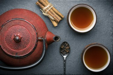 Tea composition with ceramic tea cups and red iron teapot on dark stone background