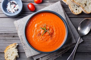 Tomato cold soup recipes in a black bowl on wooden background. Top view. Copy space