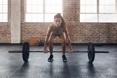 Female performing deadlift exercise with weight bar