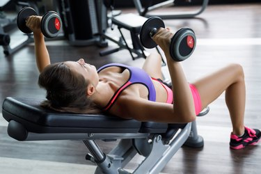 Woman working out with dumbbells in gym. Incline bench press.