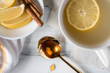 High Angle View Of Honey With Lemons On Table