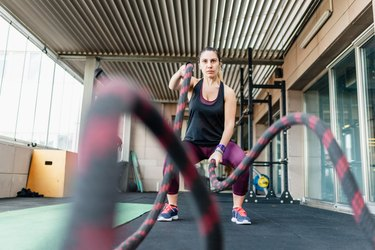 Woman using training rope for exercise at gym