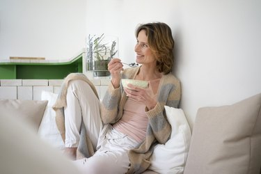 Relaxed smiling mature woman sitting on bench eating healthy food