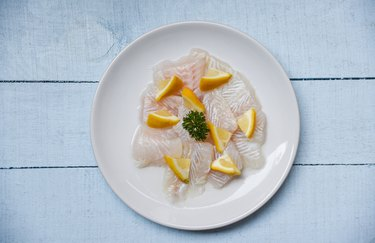 Raw fish fillet piece with lemon on white plate - Close up pangasius dolly fish meat