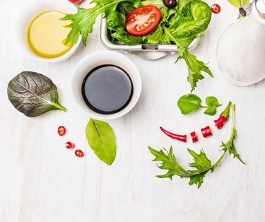 Salad preparation with oil and balsamic vinegar on white wooden