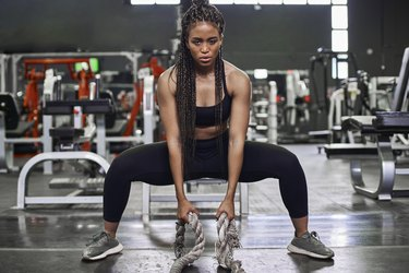 Female athlete doing strength training with heavy ropes in gym