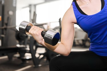hand of a woman performing exercise with dumbbell in the gym