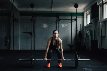Determined young woman doing deadlift in the gym