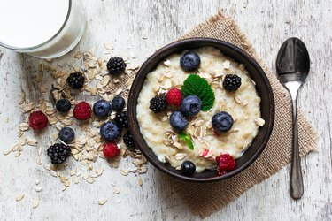 oatmeal porridge with fresh berries, glass of milk and spoon