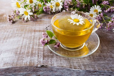 Cup of green herbal camomile tea and herbs