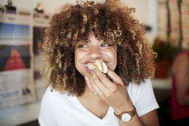 A black woman biting into a sandwich