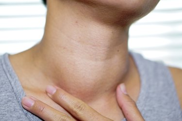 Asian lady woman patient have abnormal enlargement of thyroid gland Hyperthyroidism (overactive thyroid) at the throat : healthy strong medical concept