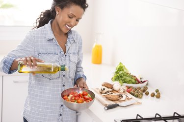 Smiling woman adding olive oil to the salad, foods good for liver health