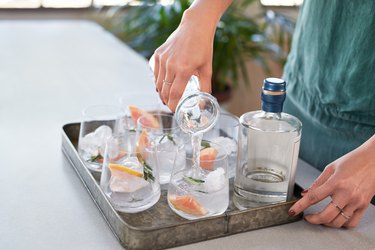 Anonymous woman's hands pouring drinks into glasses in a drinks tray