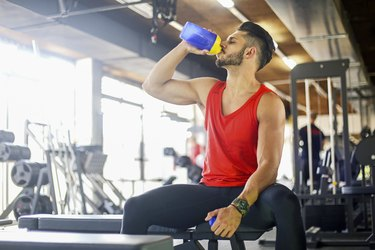 Young muscular man drinking a pre-workout supplement drink at the gym