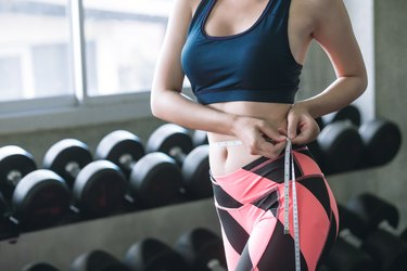 Midsection Of Woman Measuring Waist While Standing In Gym