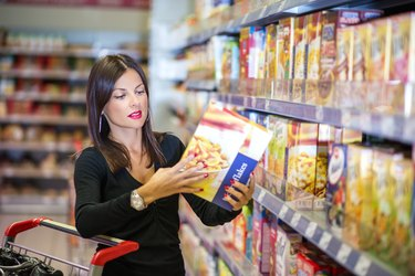Woman checking food labeling in supermarket