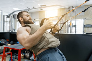 Muscular bearded man dressed in military weighted armored vest doing exercises using straps systems in the gym. Sport, training, bodybuilding and healthy lifestyle concept.