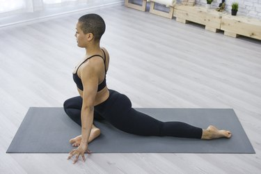 Woman Doing Pigeon Pose on Her Yoga Mat at Home