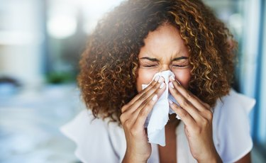 woman with allergies blowing her nose too hard, which can cause a nosebleed