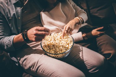 couple watching movie together and eating popcorn