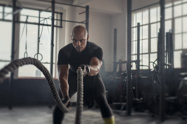 Mature strong man doing battle rope exercises during a CrossFit MetCon workout