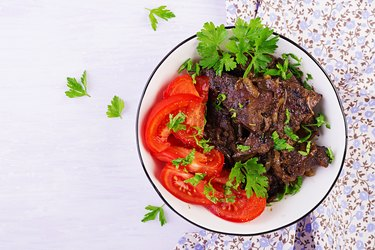 Roasted or grilled beef liver with onion and tomatoes salad. Middle Eastern cuisine. Top view