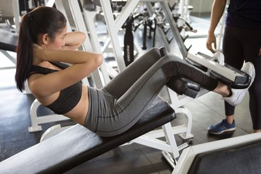 Beautiful Asian young sport woman exercise doing sit ups on the bench in fitness gym healthy .Muscular girl in sportswear training abs with trainer workout.bodybuilding Muscular six pack