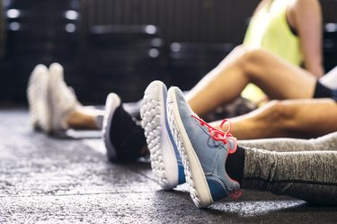 Ankles of athletes sitting on floor in gym