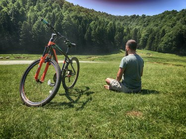 Man practicing yoga for cyclists next to his bike outdoors