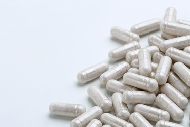 Heap of white capsules medications on white background