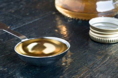 Close-Up Of White Wine Vinegar In Tablespoon On Wooden Table