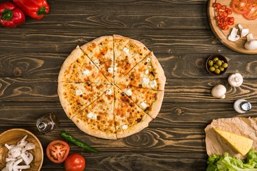 top view of cheese pizza with ingredients and vegetables on wooden table