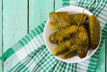 Pickled cucumbers on  wooden background.