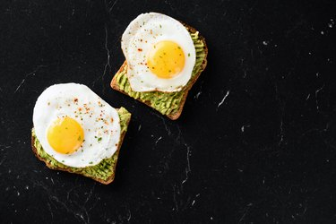Fried egg and mashed avocado on toasted bread in daily cholesterol intake