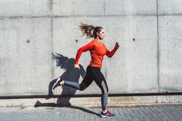 woman in red longsleeve and black leggings running outside