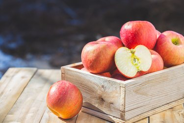 Red apples in wooden boxes on the table . Copy space.