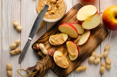 Flat lay view at Cut board with apple slices with peanut butter on white wooden kitchen table