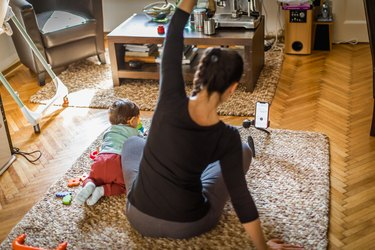 Mother exercising with her baby at home