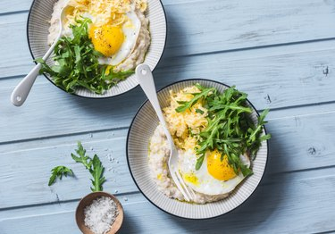 Low-FODMAP recipe oatmeal with fried egg and arugula on a blue background
