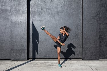 Woman doing a HIIT workout for abs by high kicking near a grey cement wall