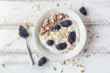 Breakfast bowl with homemade granola, dried fruits, blackberries and almond yogurt