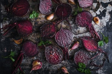 Roasted beetroots and garlic on baking sheet