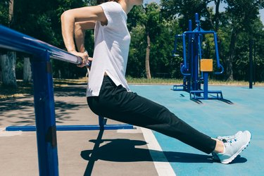 Close-up of a young athletic woman doing exercises for the triceps on the playground in the summer