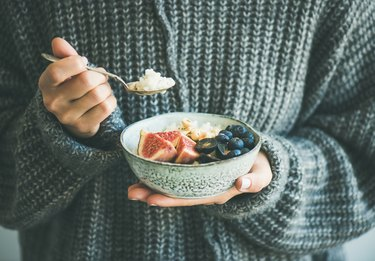 Woman in woolen sweater eating rice coconut porridge