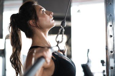 Woman strength training in weight room with confidence.