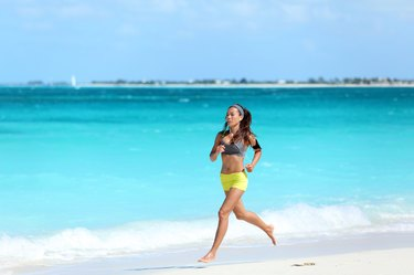 Woman runner running on beach - summer exercise