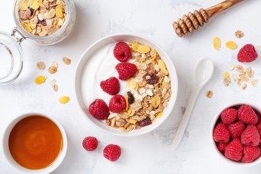 Greek yogurt in bowl with raspberries, honey and muesli on white stone table top view. Healthy diet breakfast.