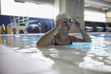 Serious female swimmer adjusting swimming goggles in swimming pool