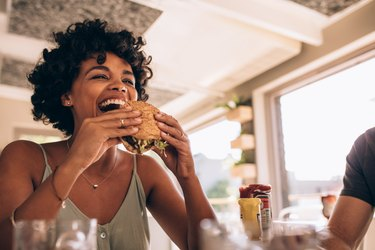 Woman enjoying eating a burger at a restaurant